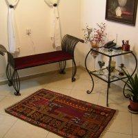 ספסל ושולחן עשויים ברזל בכניסה לבית