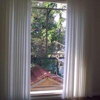חלונות בלגיים בבית פרטי מאחורי וילון